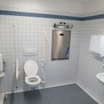 En fastmonteret toiletforhøjer med armstøtte giver ekstra sikkerhed